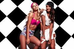 La brune et les modèles blonds dans le rnb dénomment des vêtements posant près du mur d'échecs Images libres de droits