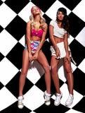 La brune et les modèles blonds dans le rnb dénomment des vêtements posant près du mur d'échecs Images stock