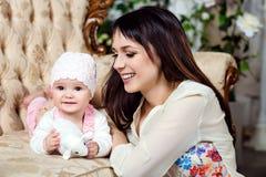 La brune heureuse et belle de maman regarde le petit DA avec du charme Photographie stock