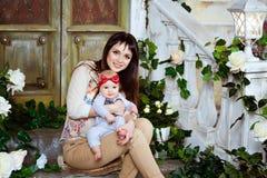 La brune heureuse et belle de maman tient son bébé adorable DA Photo libre de droits