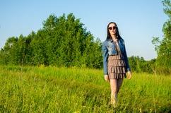 La brune marche sur un pré vert Images stock
