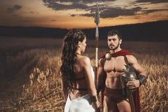 La brune portant comme le guerrier de la Grèce et de l'homme aiment spartiate Images libres de droits