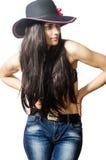 La brune posant dans un chapeau et des blues-jean image libre de droits