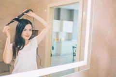 La brune se tient au miroir et à l'aide des cheveux de bigoudi Elle est dans la salle de bains La femme tient le bigoudi avec les photos libres de droits