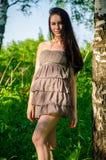 La brune se tient près du bouleau dans la forêt Photographie stock