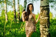 La brune se tient près du bouleau dans la forêt Photo stock