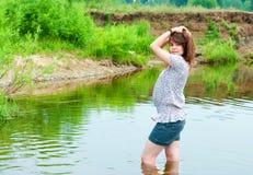 La brune sexuelle contre la rivière Image stock