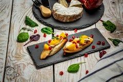 La bruschette savoureuse avec la mangue, le fromage de camembert et la grenade a servi sur un panneau de schiste, table en bois r image libre de droits