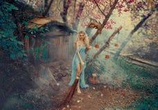 La buena bruja, la hada madrina de la Cenicienta, baila y canta mientras que limpia el patio de su pequeño imagen de archivo libre de regalías