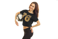La buena muchacha hermosa con el balón de fútbol se coloca en el estudio y la presentación para la cámara Fotografía de archivo libre de regalías