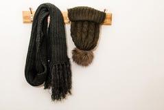 La bufanda del invierno y el casquillo de las lanas con una bola peluda y la ejecución en un sombrero se colocan Imágenes de archivo libres de regalías