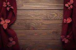 La bufanda hecha punto del color de Borgoña con las hojas de otoño en una oscuridad corteja Imagen de archivo
