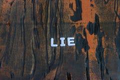 La bugia di parola scritta nei caratteri in grassetto bianchi fotografie stock libere da diritti