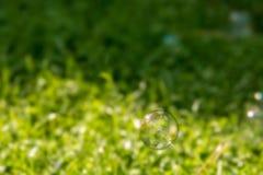 La bulle de savon vole au-dessus d'un pré images stock