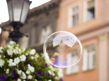 La burbuja de jabón grande vuela a través del aire en ciudad Fotografía de archivo libre de regalías
