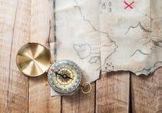 La bussola sullo scrittorio di legno con i pirati falsi fa tesoro la vecchia mappa con l'incrocio del segno rosso fotografia stock