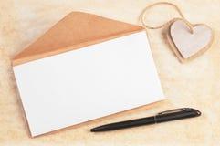 La busta con il foglio bianco ha decorato i cuori e la penna del cartone su vecchio fondo di carta con spazio per testo Fotografie Stock