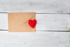La busta con una lettera e un cuore rosso di legno si trova su un wo Fotografie Stock