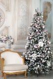La butaca está en la sala de estar, adornada por el Año Nuevo con un árbol de navidad hermoso y las guirnaldas Fotos de archivo libres de regalías