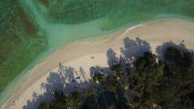 La cámara aérea del abejón que asciende y que gira arriba sobre los pares en el amor que miente en el sol en la playa acuesta sil almacen de video