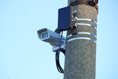 La cámara de vídeo en la chaqueta termal sellada en el soporte se fija en un pilar del camino concreto imagenes de archivo