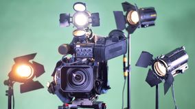 La cámara de vídeo profesional está dando vuelta con varias plantas de la iluminación en el fondo metrajes