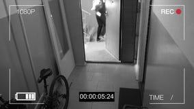 La cámara de vigilancia cogió al ladrón en una máscara que se fugaba con un bolso del botín metrajes