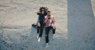 La cámara del abejón inclina abajo en pares románticos felices del blogger con el telecontrol que miente junta en una roca entre  almacen de video