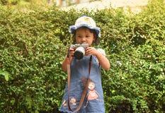 La cámara del niño toma a fotografía de la foto el niño joven del fotógrafo que toma las fotos con la cámara Foto de archivo