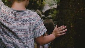 La cámara del primer sigue a dos niños que caminan cuidadosamente en las rocas grandes que caminan abajo sobre la cascada de la s almacen de metraje de vídeo