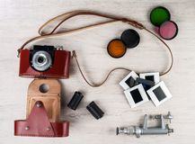 La cámara del vintage en un caso de cuero, los casetes, los filtros de color, las diapositivas y un mini soporte en la tabla emer fotografía de archivo libre de regalías