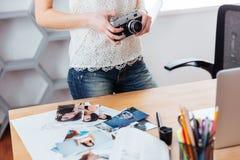 La cámara del vintage holded por el fotógrafo de la mujer joven que se colocaba en oficina Imagen de archivo