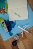 La cámara digital, la lechería, la pluma, el mapa, el compás y el aeroplano modelan Fotos de archivo libres de regalías