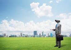 La cámara dirigió al hombre que se oponía en hierba verde a paisaje urbano moderno Imágenes de archivo libres de regalías