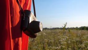 La cámara en un caso es tomada por la mano femenina al aire libre en un campo en verano en el slo-MES metrajes