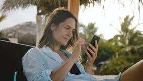 La cámara enfoca adentro en la mujer joven hermosa feliz usando el app del smartphone que sonríe, descansando en silla exótica de almacen de metraje de vídeo