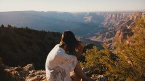La cámara enfoca adentro en la mujer joven pacífica con el pelo del vuelo que mira panorama épico de la puesta del sol sobre la c almacen de metraje de vídeo