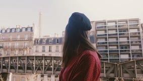 La cámara enfoca adentro en la mujer turística caucásica feliz joven que sonríe en el balcón soleado de París con la cámara lenta metrajes