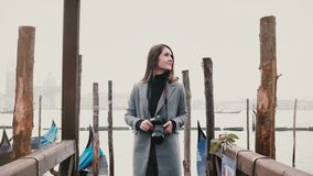 La cámara enfoca hacia fuera en mujer turística sonriente feliz con la cámara que toma las fotos en el embarcadero romántico de l metrajes