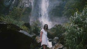 La cámara inclina abajo para revelar la presentación hermosa joven feliz de la mujer, disfrutando de la naturaleza en la cascada  metrajes