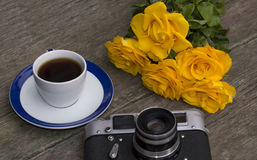 La cámara, las rosas y el café viejos de la película en una tabla de madera Imagen de archivo libre de regalías