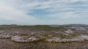 La cámara lenta agita en una costa del lago Michigan de la playa de la arena