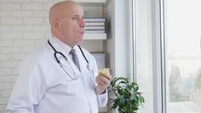 La cámara lenta con el doctor en oficina del hospital toma una pausa que come Apple fresco metrajes