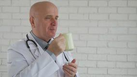 La cámara lenta con el doctor Taking una rotura de trabajo activa la consumición de una taza de café almacen de video