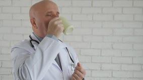 La cámara lenta con el doctor Taking una rotura de trabajo activa la taza de café caliente de consumición almacen de video
