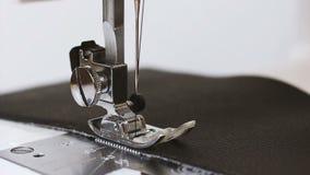 La cámara lenta de la aguja con el hilo de la máquina de coser cose la tela de cuero almacen de metraje de vídeo