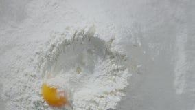 La cámara lenta de caer eggs en la acción de la harina Comida de la cantidad Egg la caída en la harina, cámara lenta La yema de h almacen de metraje de vídeo