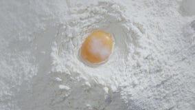 La cámara lenta de caer eggs en la acción de la harina Comida de la cantidad Egg la caída en la harina, cámara lenta La yema de h metrajes
