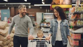 La cámara lenta de la familia feliz de la gente alegre que corre en tienda de alimentación con la carretilla de las compras y que almacen de video