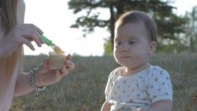La cámara lenta de la madre alimenta verduras de la hija en puesta del sol de la llamarada almacen de metraje de vídeo